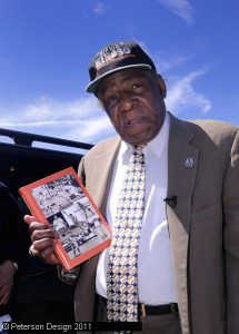 Image of Minnie Minoso holding book authored by Bryan Steverson